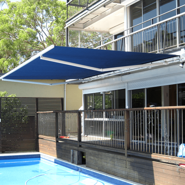 Folding Arm Awning with blue fabric hanging above a swimming pool. Comfort model from covered group