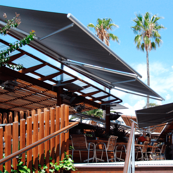 Comfort Folding Arm Awning installed over alfresco seated dining area with grey fabric and silver powder coating