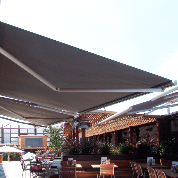 View from below Comfort Folding Arm Awning installed over alfresco seated dining area with grey fabric and silver powder coating