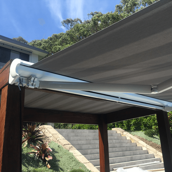 Underside photo of Comfort Folding Arm Awning with Grey and White block Stripe acrylic fabric over pool area with bush surround landscaping by Outdoor Aussie