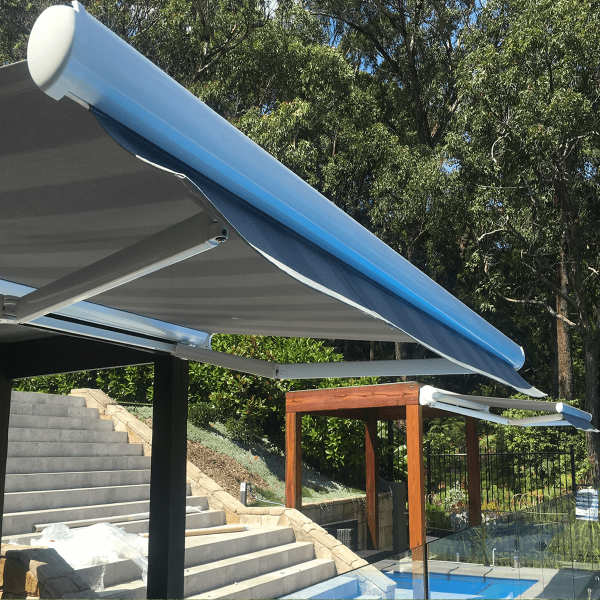 Two twin Comfort Folding Arm Awnings with Grey and White block Stripe acrylic fabric over pool area with bush surround landscaping by Outdoor Aussie