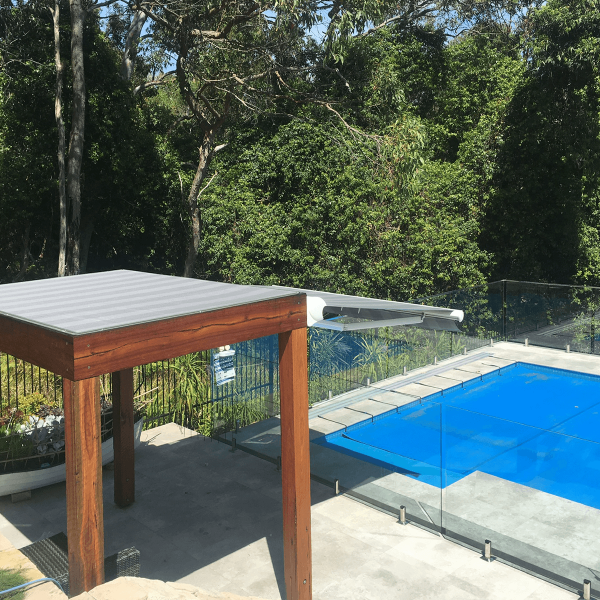Top view photo of Comfort Folding Arm Awning with Grey and White block Stripe acrylic fabric over pool area with bush surround landscaping by Outdoor Aussie