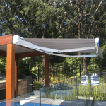 Comfort Folding Arm Awning with Grey and White block Stripe acrylic fabric over pool area with bush surround landscaping by Outdoor Aussie