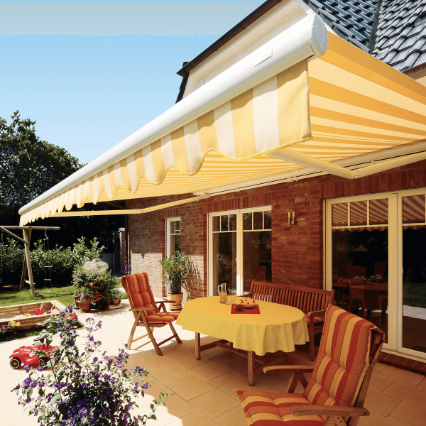Yellow and white striped fabric on comfort Folding Arm Awning over outdoor dining alfresco area