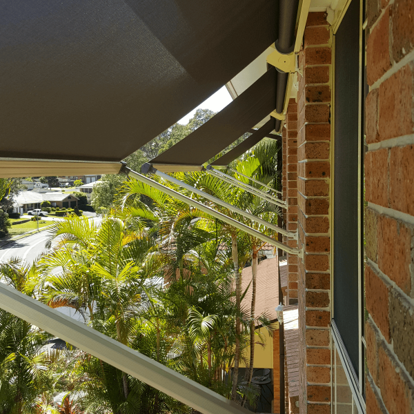 Side view of three S2000 Pivot Arm Awnings on second storey of brick home