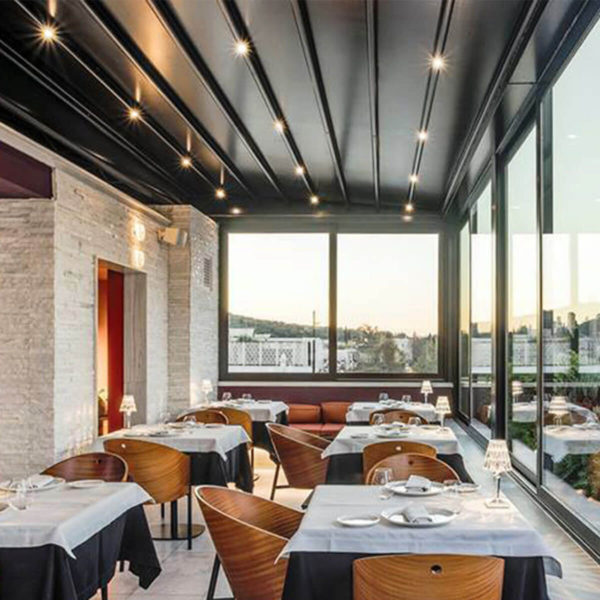 Chocolate coloured Zerro retractable roof system enclosing restaurant with glass windows and LED lights