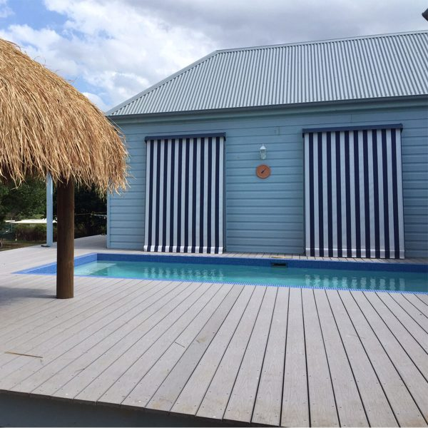 Black and white block striped canvas automatic awning on beach house near beach hut